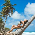 Модель в черном купальнике позирует на пляже Макао