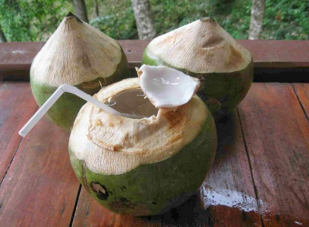 Открытый молодой кокос с трубочкой и кокосовым молоком