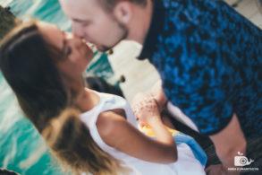 Нежный поцелуй жениха и невесты возле океана