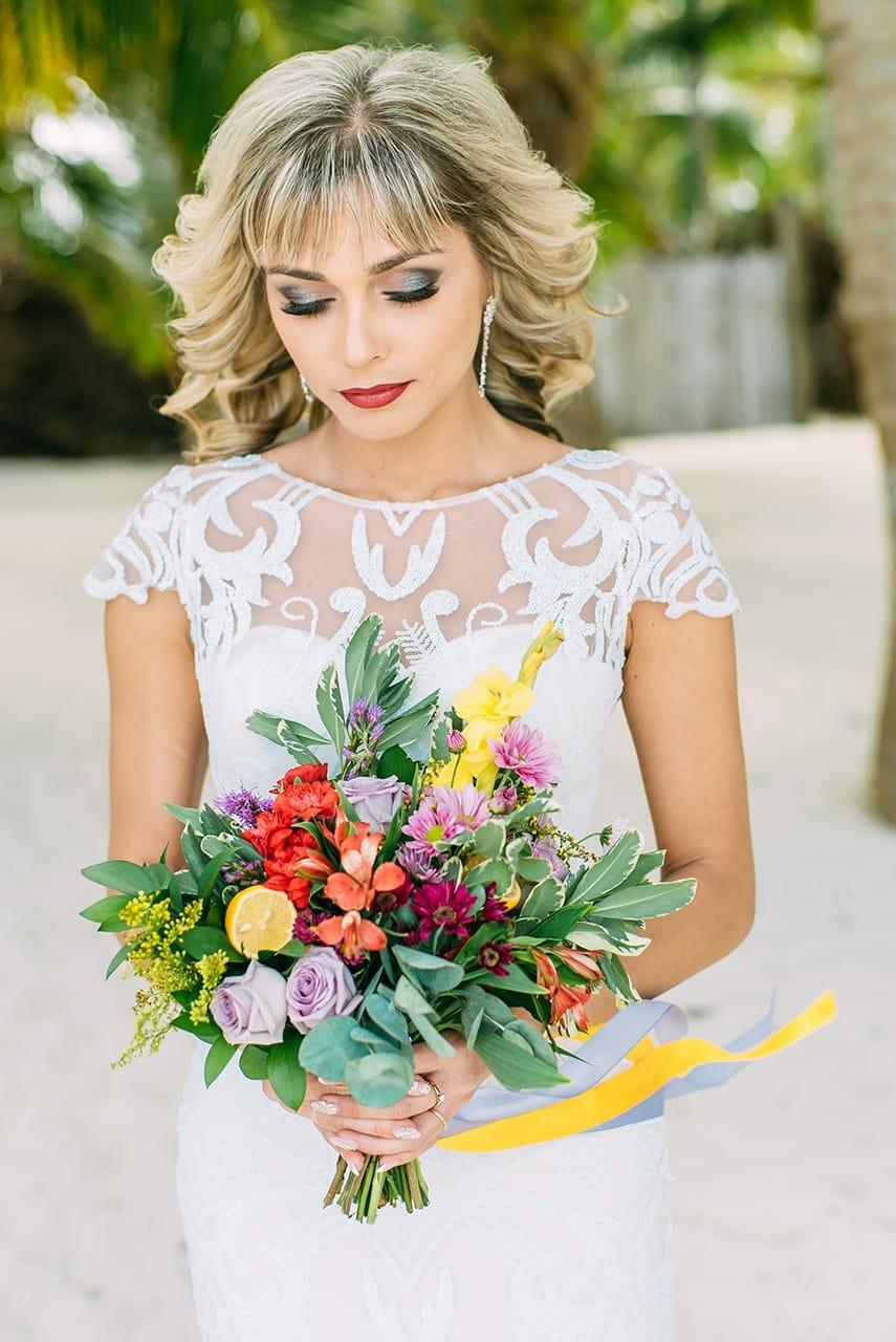 Невеста в белом платье с разноцветным свадебным букетом