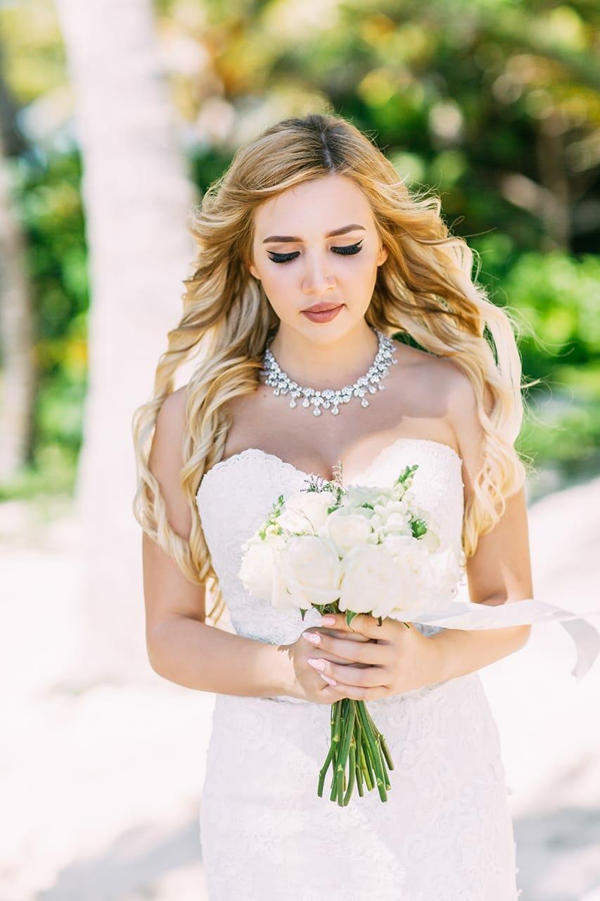 Невеста в белом платье с белым свадебным букетом