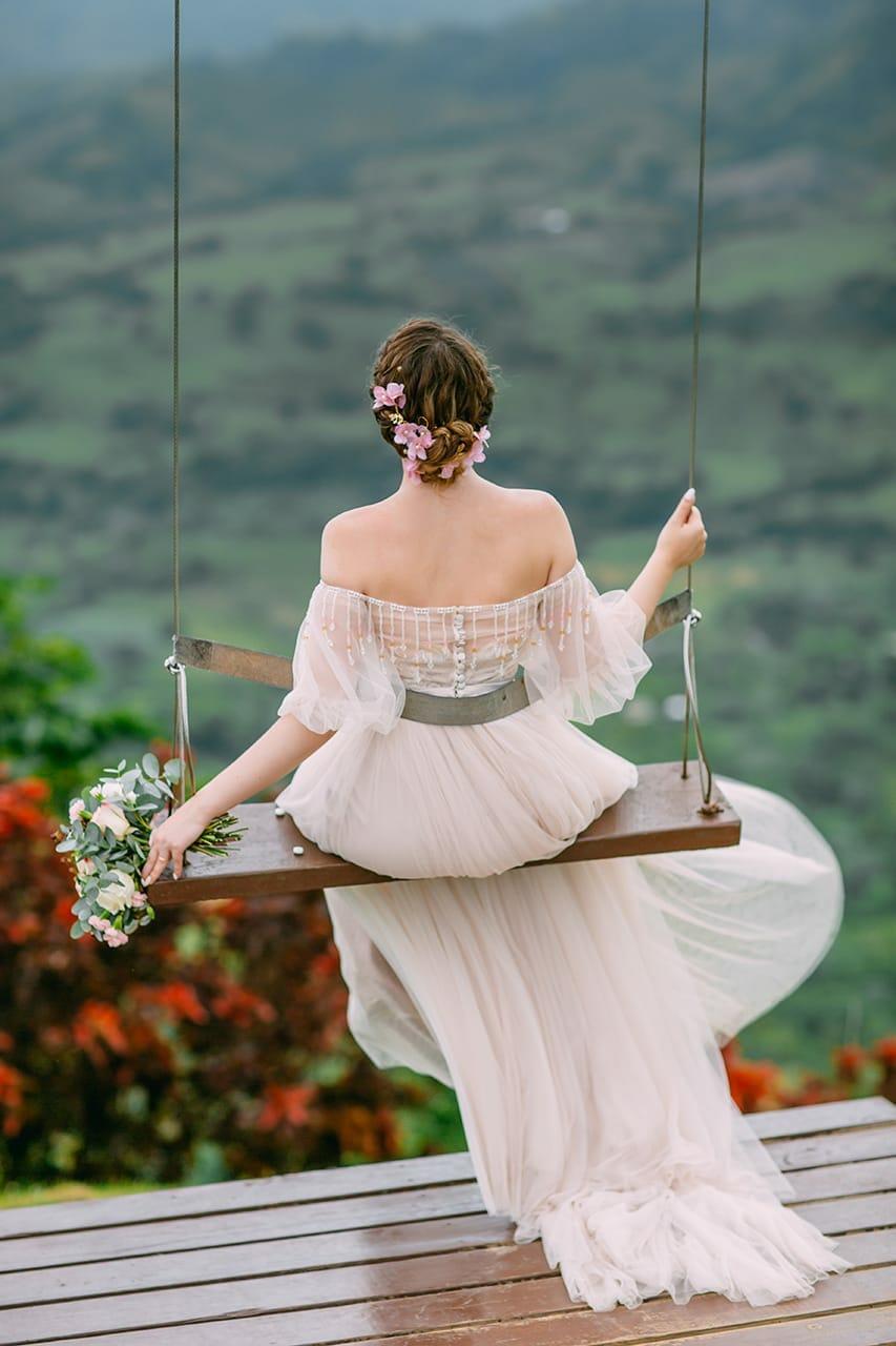 невеста в платье с букетом качается на качелях