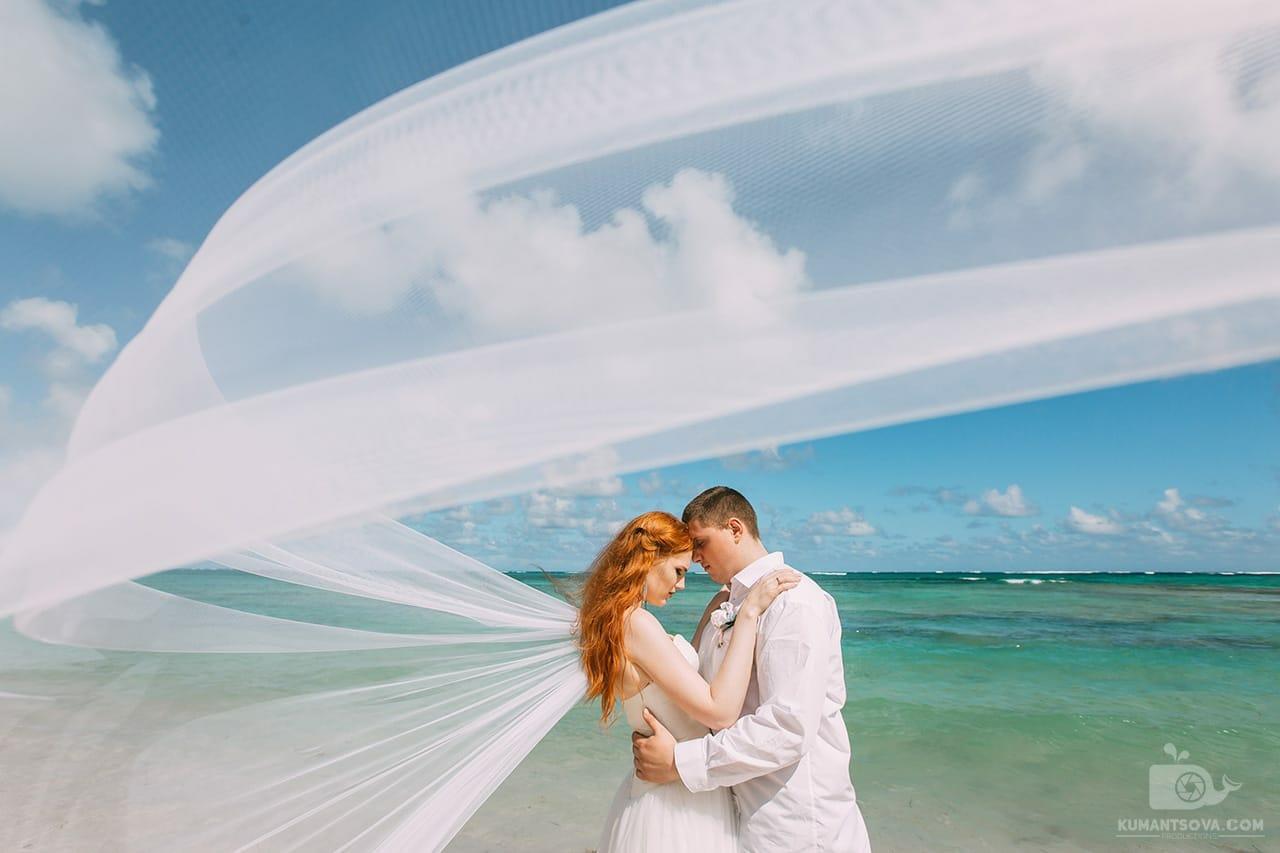 Невеста с фатой обнимает жениха на пляже